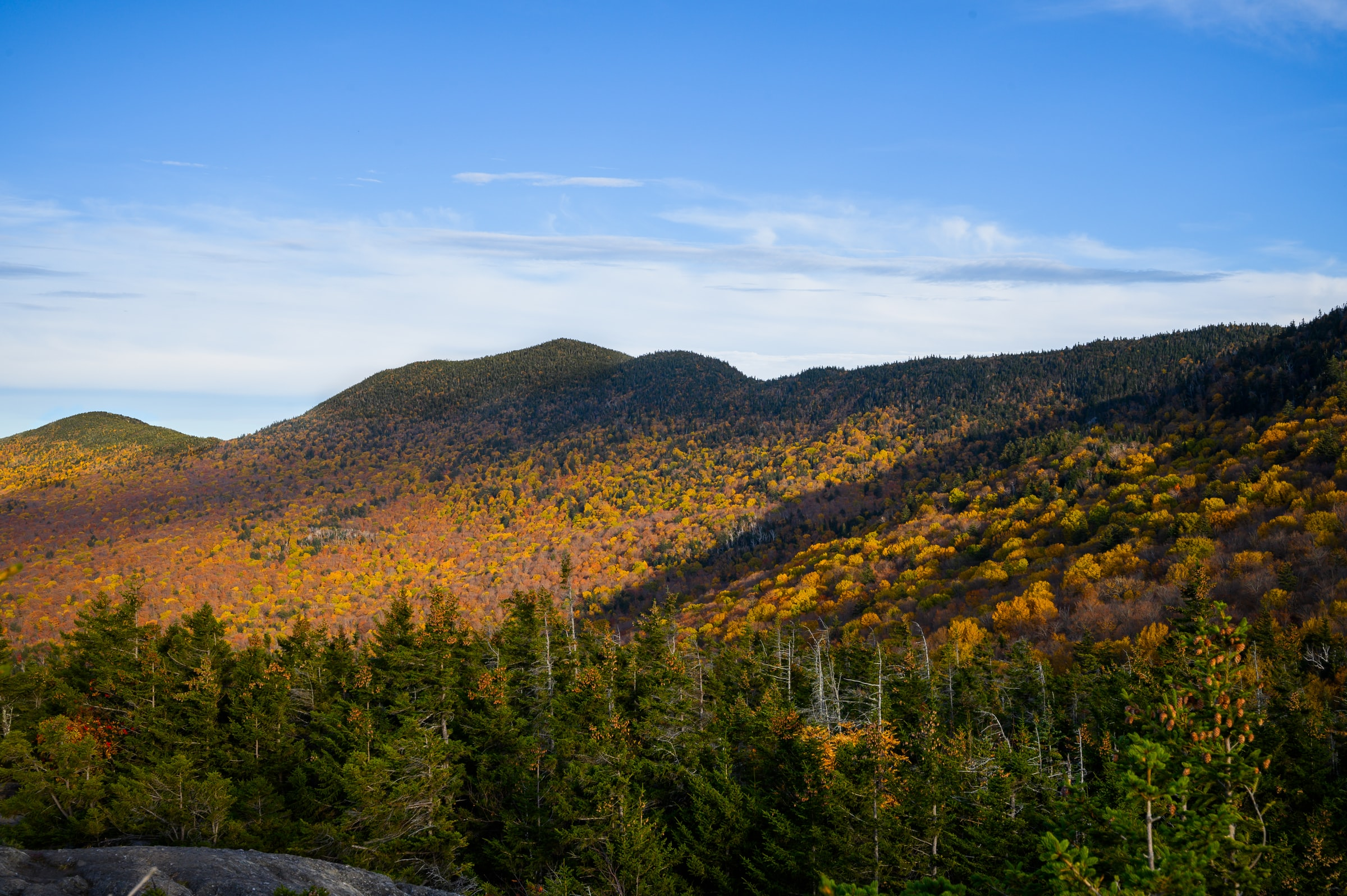 Vermont daytime sky over mountains with foliage.